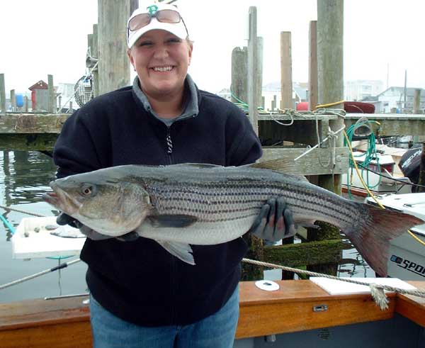 "She is obviously pleased with this 37"" 17lb Striped Bass."